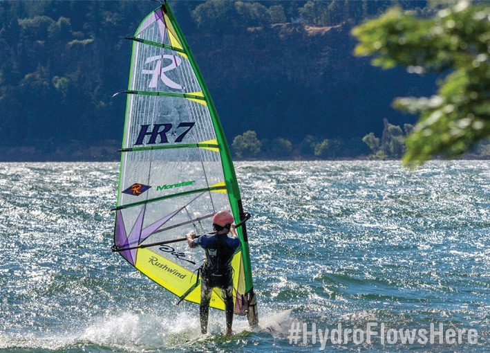 Photo of wind surfer on a river. Text: #HydroFlowsHere