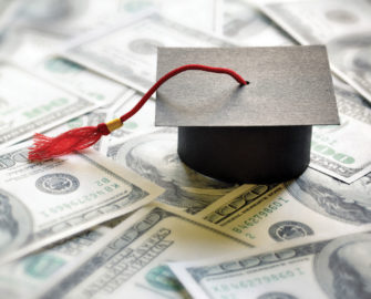 small cardboard graduation cap on money