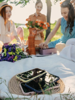 group of girls having picnic outside with their phones in a basket to the side