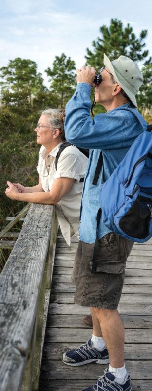 A woman on a bridge with a man looking through binoculars