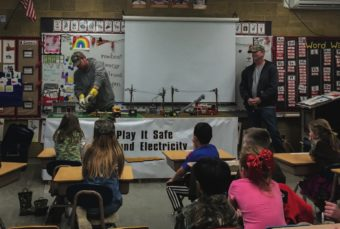 Wasco Electric linemen Dan Funkhouser, Andy Gardipee and BJ Ayres show first and third graders the importance of staying safe around electricity.