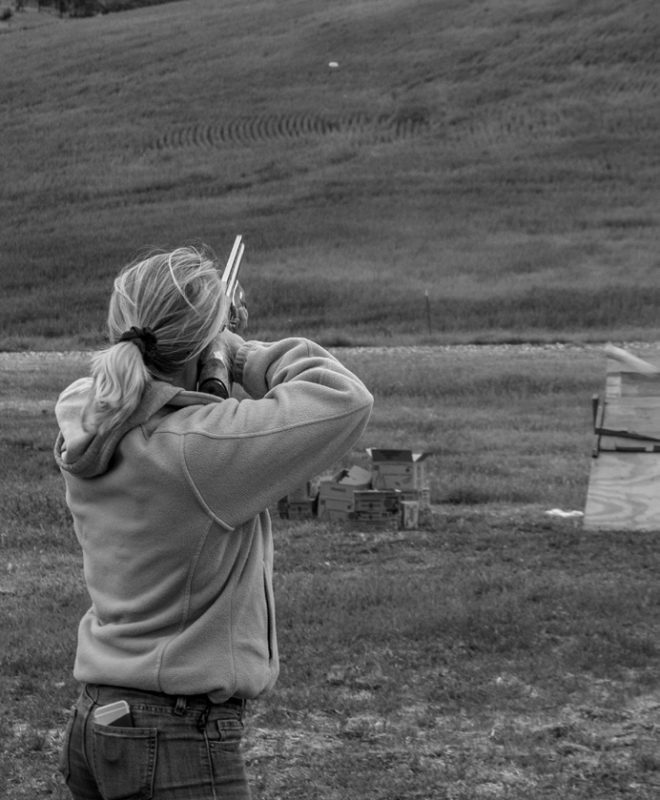 Jessica Elam takes aim at a trap shooting target in the distance.