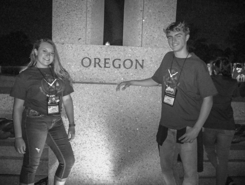 Linnae and Thomas pose for a photo in front of the Oregon marker at the National World War II Memorial.