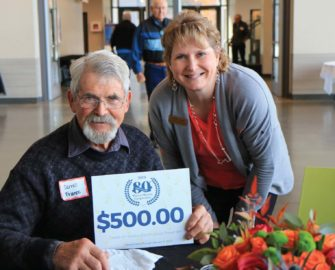 Executive Staff Assistant Jennifer Lindsey presents the $500 grand prize to Darrell France.
