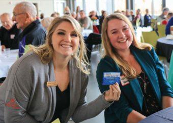 Customer Service Representative Kelsey Lepinski presents a gift card to kids' grand prize winner Linnae Roeder.