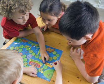 Group of young children playing a board game