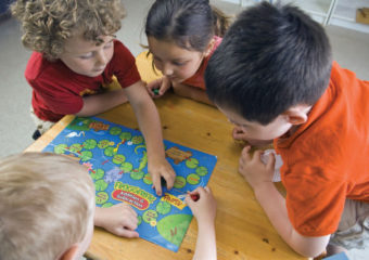 Group of young children playing a boardgame.