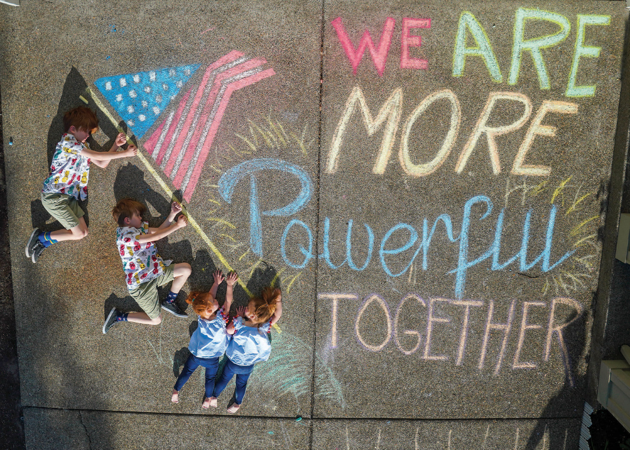 Four young children, holding onto the flagpole chalked on their driveway. We are more powerful together.