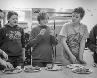 several students displaying and discussing the meals they prepared in their afterschool cooking class